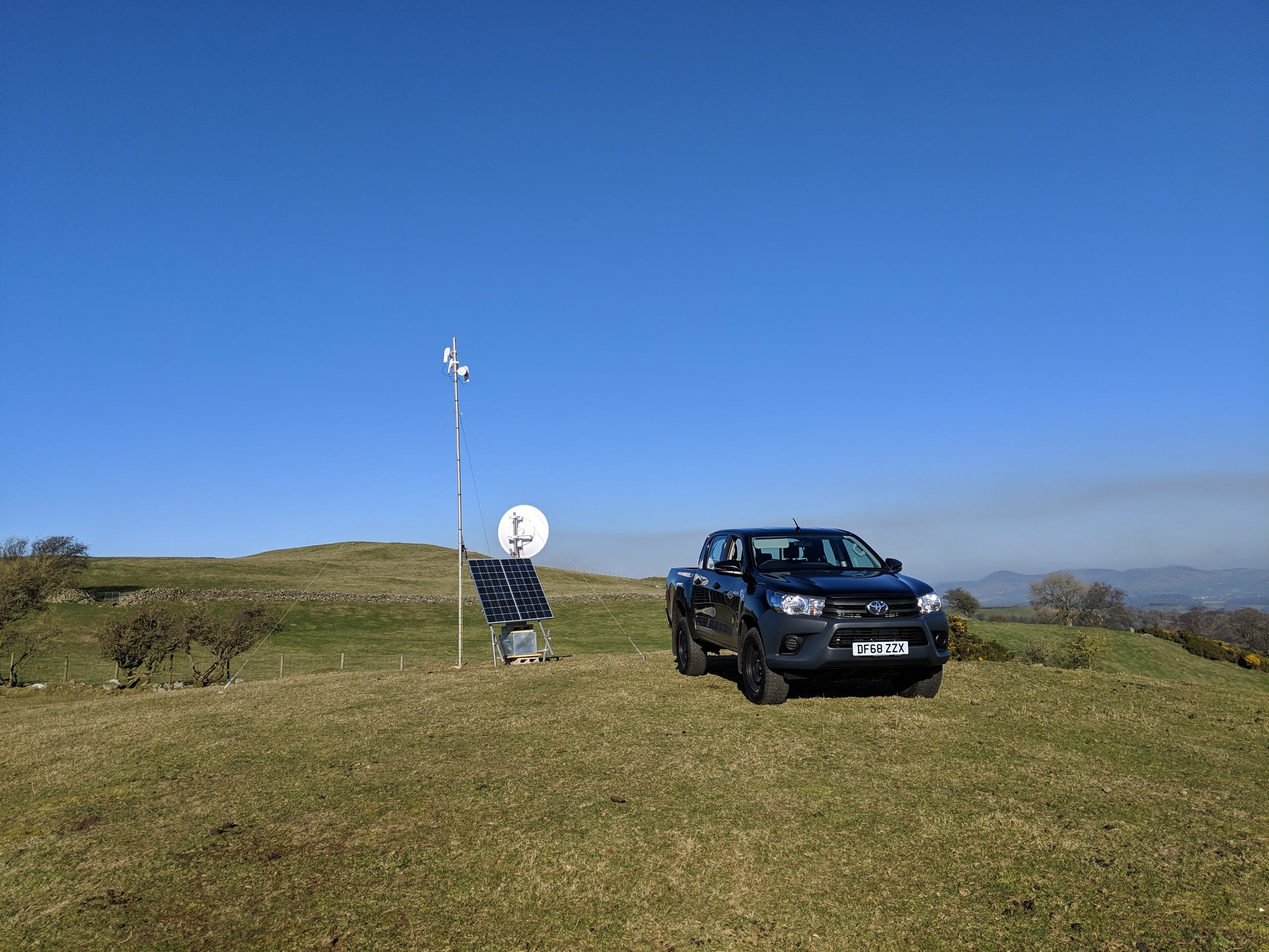 A view of a mast with a pickup truck on a hill